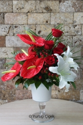 Red anthurium, red roses and white lilies arranged in a glass vase with glass of share happiness.